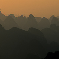 Early morning light over landscape of myriad silhouetted karst towers, Yangshuo, Guilin, China