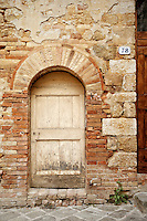 Photo of a rustic, rounded door surrounded by stone along the streets of San Quirico d'Orcia, Italy.