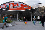 With new local coronavirus lockdown measures now in place and Birmingham currently set at 'Tier 2' or 'high', people wearing face masks pass beneath a public health advice advertising campaign featuring Bully the Bull Ring bull wearing a face mask with the slogan 'It's NO bull. Keep Brum safe' outside Grand Central station in the city centre on 14th October 2020 in Birmingham, United Kingdom. This is the first day of the new three tier system in the UK which has levels: 'medium', which includes the rule of six, 'high', which will cover most areas under current restrictions; and 'very high' for those areas with particularly high case numbers. Meanwhile there have been calls by politicians for a 'circuit breaker' complete lockdown to be announced to help the growing spread of the Covid-19 virus.