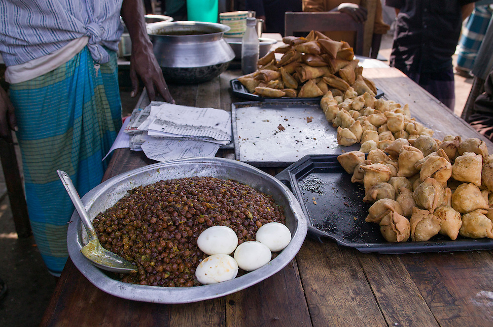 A road side food vendor selling samosa's, and beans and eggs in Bangladesh.