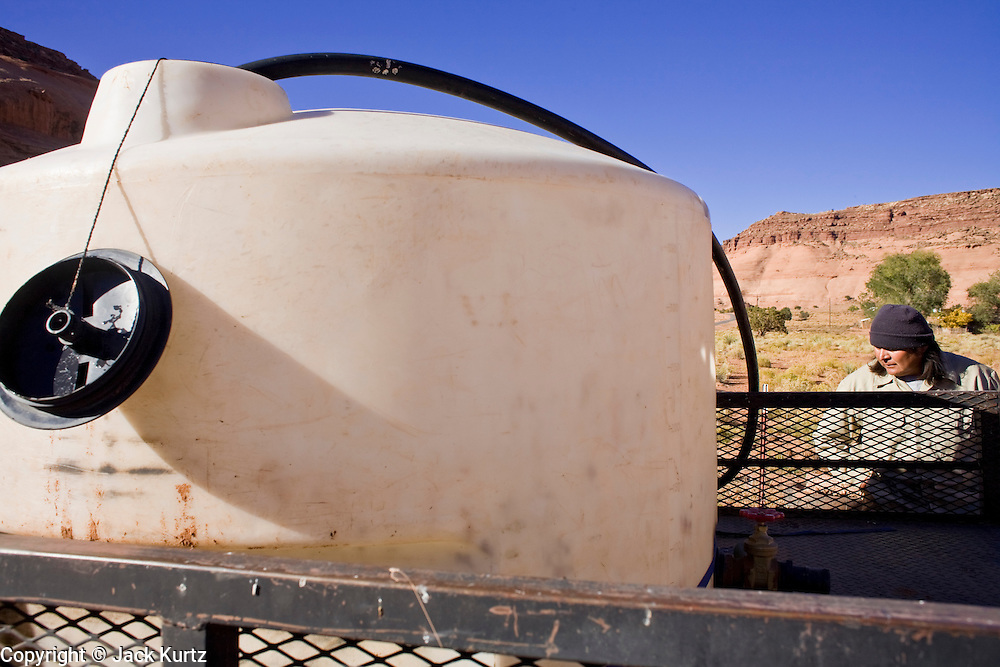 22 OCTOBER 2007 -- MONUMENT VALLEY, UT: LARRY ATENE, Navajo Indians living on the Navajo Reservation in southern Utah, fills a 400 gallon tank with potable water at the well at Goulding's Trading Post near Monument Valley, UT. The well at Goulding's was first dug by Seventh Day Adventists missionaries and is the only source of clean, free water for miles around. More than 30 percent of the homes on the Navajo Nation, about the size of West Virginia and the largest Indian reservation in the US, don't have indoor plumbing or a regular supply of domestic water. Many of these homes have to either buy water from commercial vendors or haul water from public wells. A Federal study showed that the total cost of hauling water was about $113 per 1,000 gallons. A Phoenix household, in comparison, pays just $5 a month for up to 7,400 gallons of water. The lack of water on the reservation means the Navajo are among the most miserly users of water in the United States. Families that have to buy or haul water use only about 15 gallons of water per day per person. In Phoenix, by comparison, the average water use is about 170 gallons per day.  Photo by Jack Kurtz