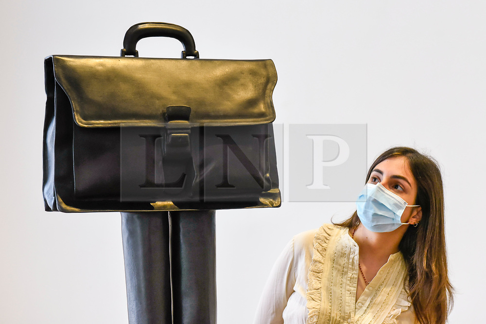 """© Licensed to London News Pictures. 16/06/2020. LONDON, UK. A staff member wearing a facemask views """"Direktor (Herrentasche) (Taschenskulpturen)"""", 2019, by Erwin Wurm on the opening day of a new exhibition """"Art Basel at Ely House"""" taking place at Galerie Thaddaeus Ropac in Mayfair.  The commercial gallery has implemented social distancing guidelines for visitors for its reopening after coronavirus pandemic lockdown restrictions were relaxed by the UK government.  The exhibition runs 16 June to 31 July 2020.  Photo credit: Stephen Chung/LNP"""
