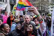 LGBTI rights campaigner Peter Tatchell has a selfie photograph taken with protesters. Demonstrators gather outside the Dorchester Hotel in Park Lane in London, England, United Kingdom on 6th April, 2019 to protest against new Islamic criminal laws ratified by  the Sultan of Brunei punishing homosexuality by stoning offenders to death. The hotel is owned by the Sultan of Brunei.
