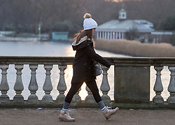 © Licensed to London News Pictures. 11/02/2021. London, UK. A woman in winter clothing walks through Hyde Park, central London, following another night of sub zero temperatures in the capital. Photo credit: Ben Cawthra/LNP