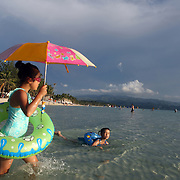 Young children enjoy the pristine waters of White Beach,  Boracay Island, the Philippines on October 3, 2008, Photo Tim Clayton..Asian tourists at White Beach, Boracay Island, the Philippines...The 4 km stretch of White beach on Boracay Island, the Philippines has been honoured as the best leisure destination in Asia beating popular destinations such as Bali in Indonesia and Sanya in China in a recent survey conducted by an International Travel Magazine with 2.2 million viewers taking part in the online poll...Last year, close to 600,000 visitors visited Boracay with South Korea providing 128,909 visitors followed by Japan, 35,294, USA, 13,362 and China 12,720...A popular destination for South Korean divers and honeymooners, Boracay is now attracting crowds of tourists from mainland China who are arriving in ever increasing numbers. In Asia, China has already overtaken Japan to become the largest source of outland travelers...Boracay's main attraction is 4 km of pristine powder fine white sand and the crystal clear azure water making it a popular destination for Scuba diving with nearly 20 dive centers along White beach. The stretch of shady palm trees separate the beach from the line of hotels, restaurants, bars and cafes. It's pulsating nightlife with the friendly locals make it increasingly popular with the asian tourists...The Boracay sailing boats provide endless tourist entertainment, particularly during the amazing sunsets when the silhouetted sails provide picture postcard scenes along the shoreline...Boracay Island is situated an hours flight from Manila and it's close proximity to South Korea, China, Taiwan and Japan means it is a growing destination for Asian tourists... By 2010, the island of Boracay expects to have 1,000,000 visitors.