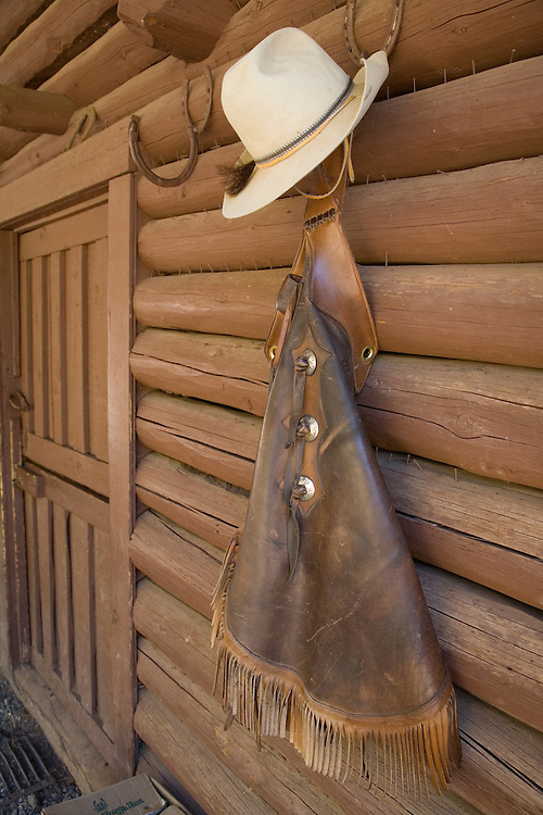United States, Montana, Livingston, cowboy hat and chaps hanging on barn wall