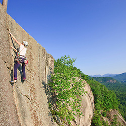 """A woman leads a climb of """"Top of the Prow"""" on Cathedral Ledge.  Echo Lake State Park in North Conway, New Hampshire.  White Mountains."""