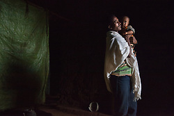 Addisu, 27, stands with his son inside the home he shares with his 15-year-old wife Destaye near Bahir Dar, Ethiopia on Aug. 11, 2012. The couple divide their time between working in the fields and taking care of their 6-month-old baby. Like many other young couples, they tend to the domestic, economic and personal demands of being young parents. At the time of their marriage, when Destaye was age 11, she was still in school and her husband expressed interest in letting her continue her education. Since the birth of their son, however, she has had to confine her life exclusively to being a wife and mother.