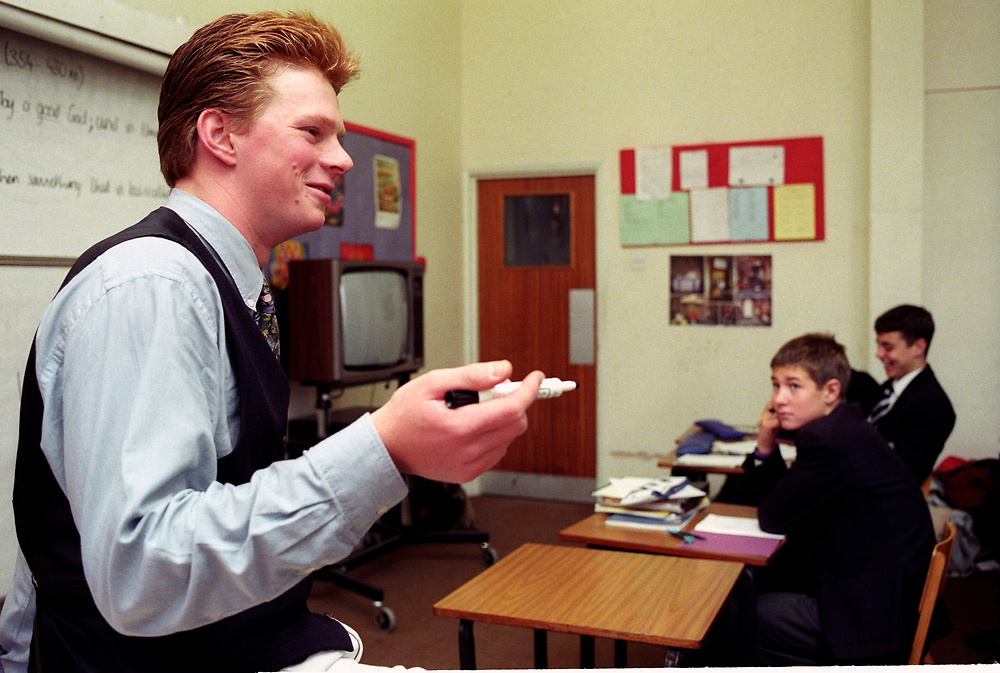 Male teacher standing in front of classroom of  secondary school pupils,