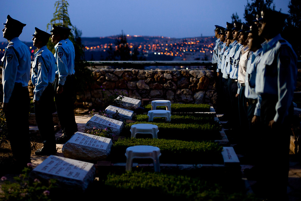 Israeli policemen stand in front of graves of fallen policemen as they attend a ceremony of laying Israel's national flag on the grave of each fallen policeman at the Mount Herzl military cemetery in Jerusalem on May 4, 2011. Israel will mark the annual Memorial Day for Fallen Soldiers next week.