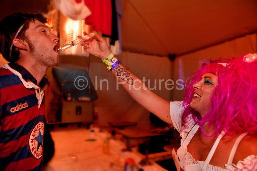 Having a shot of vodka via a syringe, the Alleys, Shangri-la, Glastonbury Festival 2010