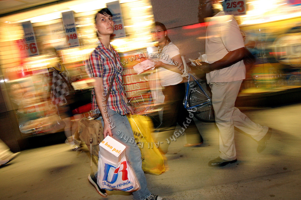 Stephanie, 21, member of the Freegan community in New York, walking along 3rd Avenue in Manhattan with two bags full of food recovered from damps sites along the road, in New York, NY., on Wednesday, June 21, 2006. Freegans are a community of people who aims at recovering wasted food, books, clothing, office supplies and other items from the refuse of retail stores, frequently discarded in brand new condition. They recover goods not for profit, but to serve their own immediate needs and to share freely with others. According to a study by a USDA-commissioned study by Dr. Timothy Jones at the University of Arizona, half of all food in the United States is wasted at a cost of $100 billion dollars every year. Yet 4.4 million people in the United States alone are classified by the USDA as hungry. Global estimates place the annual rate of starvation deaths at well over 8 million. The massive waste generated in the process fills landfills and consumes land as new landfills are built. This waste stream also pollutes the environment, damages public health as landfills chemicals leak into the ground, and incinerators spew heavy metals back into the atmosphere. Freegans practice strategies for everyday living based on sharing resources, minimizing the detrimental impact of our consumption, and reducing and recovering waste and independence from the profit-driven economy. They are dismayed by the social and ecological costs of an economic model where only profit is valued, at the expense of the environment. In a society that worships competition and self-interest, Freegans advocate living ethical, free, and happy lives centred around community and the notion that a healthy society must function on interdependence. Freegans also believe that people have a right and responsibility to take back control of their time.