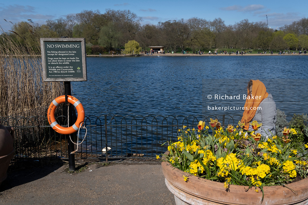 A woman wears an orange scarf over her head while resting next to an orange life buoy located on the edge of the water and a No Swimming warning sign at the Serpentine in Hyde Park, on 2nd April 2021, in London, England.