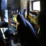 Two sisters prepare lunch consisting of potatoes, bread, chicken and soup. The pot is illuminated from a stream of light coming through the roof of the kitchen. Panjab District, Bamyan Province, Afghanistan.