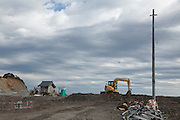 A diggers sits on cleared land by a tsunami damaged shrine near the coast in Iwaki, Fukushima, Japan. Sunday January 26th 2014
