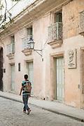 Young man walking down street with backpack, Havana, Cuba