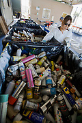 An Hispanic women sorts aerosol cans, solvents and cleaning containers. S.A.F.E  Collection Center, Sun Valley, Bureau of Sanitation for the City of Los Angeles, California, USA