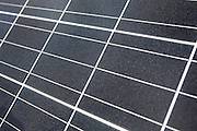 Close-up of a photovoltaic solar energy panel. This panel, or module, is made up of photovoltaic (PV) cells. PV cells convert sunlight into electrical energy. Photovoltaic panels are an economical, efficient way to produce electricity that does not pollute or contribute to global warming.