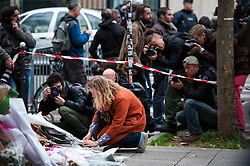 © London News Pictures. 14/11/2015. A woman laying flowers near Bataclan theater  the day after multiple terror attacks on the French capital. Photo credit: Guilhem Baker/LNP