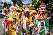 """05 JULY 2014 - BANGKOK, THAILAND: Chinese style dancers on Sukhumvit Road in Bangkok during a parade for vassa. Vassa, called """"phansa"""" in Thai, marks the beginning of the three months long Buddhist rains retreat when monks and novices stay in the temple for periods of intense meditation. Vassa officially starts July 11 but temples across Bangkok are holding events to mark the holiday all week.    PHOTO BY JACK KURTZ"""