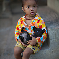 A girl cuddles a puppy in a rural area of Takéo province, Cambodia
