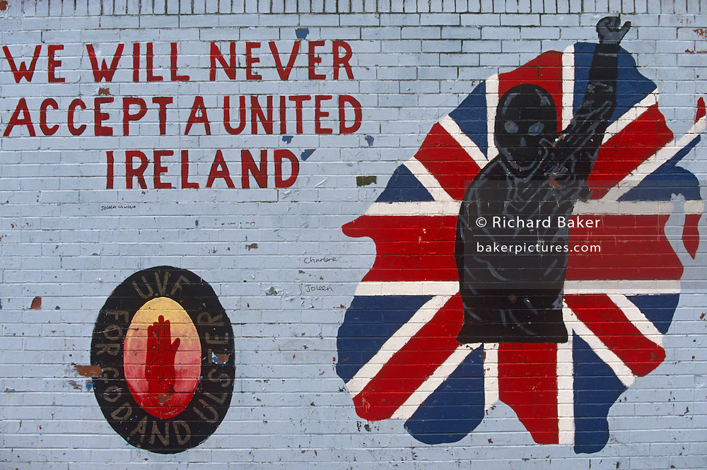 With the words 'We will never accept a united Ireland' and another quote 'For God and Ulster' we see a detail of a political painting in a street off the Shankhill Road in Belfast, Northern Ireland. This Loyalist mural may have been drawn by a paramilitary artist, whose handiwork is the crest of the protestant Ulster Defence Association (UDA) and the Ulster Volunteer Force (UVF) the organisations behind many a sectarian action against neighbouring catholic supporters of the Irish republican Army (IRA). In loyalist areas, the red, white and blue of the British Union Jack is painted on kerbs, houses and railings to signify peoples' allegiance to the crown, having historically followed the 17th century activities of King William of Orange against Catholics..