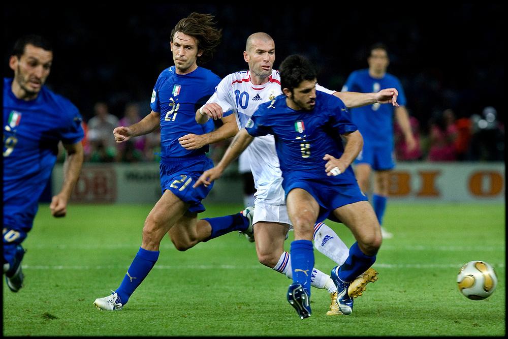 Duitsland. Berlijn, 09-07-2006<br /> WK Voetbal Finale: Italie-Frankrijk. <br /> Titelverdediger Frankrijk starte hoopvol tegen het altijd sterke Italie. Het had een mooi afscheid voor de franse voetballer moeten zijn maar Zinedine Zidane werd met een rode kaart van het veld werd gestuurd na het geven van een kopstoot aan Mazzarati. De fransen hielden lang stand maar na de verlenging en strafschoppen gingen de Italianen lachend met de Wereldbeker naar huis. Zinedine Zidane tackelt een italiaan.<br /> Foto: Patrick Post / Sportstation