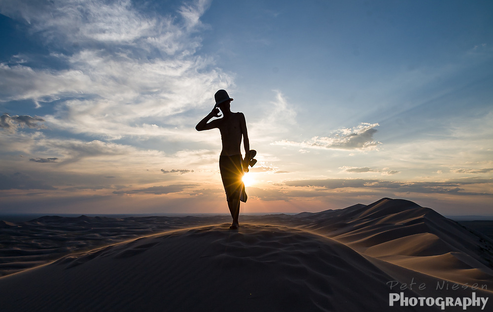 Silhouette of man on top of the dunes in the Gobi desert at sunset