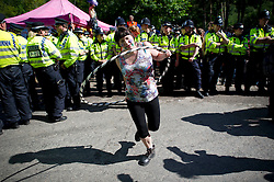 © London News Pictures. 19/08/2013. Balcombe, UK. An Activist using a hoola hoop  in front of police at the entrance to the Cuadrilla drilling site in Balcombe, West Sussex on a day of of civil disobedience organised by campaign group No Dash For Gas. Cuadrilla has temporarily ceased drilling at the site, which has been earmarked for fracking, under advice from the police. Photo credit: Ben Cawthra/LNP