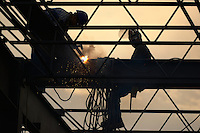 Ironworkers welding the steel framework of a building.