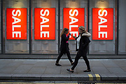Shoppers walk past Christmas Sale signs outside the H&M branch of H&M in the City of London, the capitals financial district, on 19th December 2018, in London UK.
