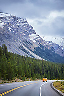 A VW van driving down the road on the Icefields Parkway in Banff National Park, Alberta, Canada