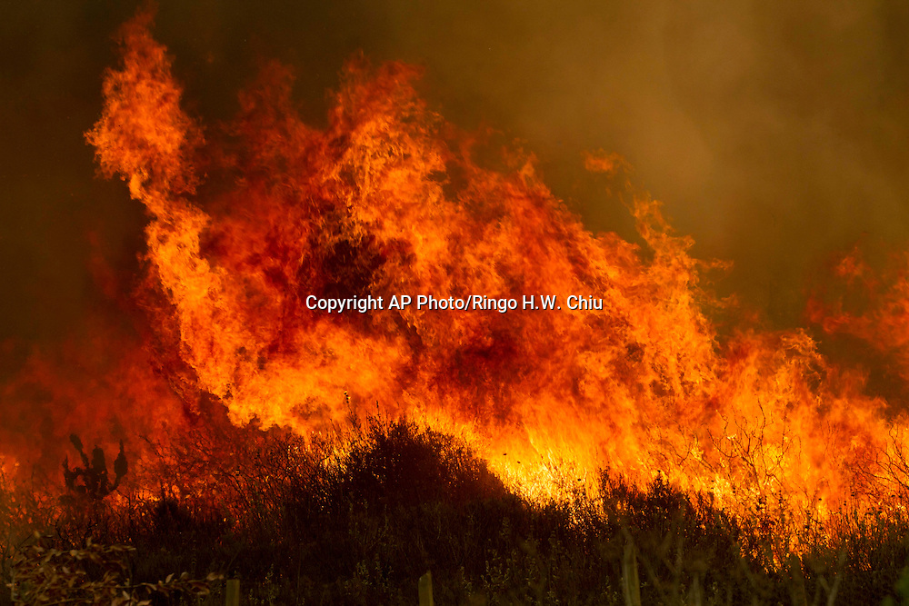 Flame is seen at  a hillside in Point Mugu , Calif. Friday, May 3, 2013..(AP Photo/Ringo H.W. Chiu)