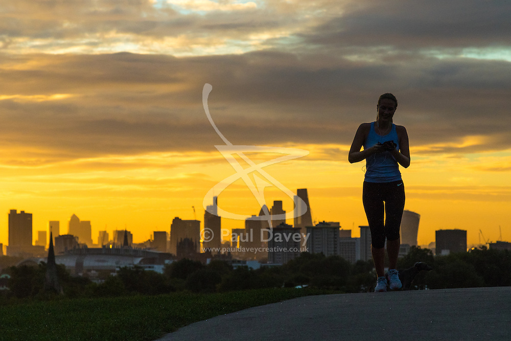 Primrose Hill, London, September 27th 2016. Skyscrapers provide impressive backdrop as a woman jogs on Primrose Hill at dawn in London. ©Paul Davey<br /> FOR LICENCING CONTACT: Paul Davey +44 (0) 7966 016 296 paul@pauldaveycreative.co.uk