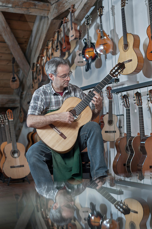 Guitar maker playing guitar in music store