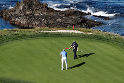 June 11, 2019 - Pebble Beach, CA, U.S. - PEBBLE BEACH, CA - JUNE 11: PGA golfers Dustin Johnson putts on the 7th hole while coach Butch Harmon holds the flag stick during a practice round for the 2019 US Open on June 11, 2019, at Pebble Beach Golf Links in Pebble Beach, CA. (Photo by Brian Spurlock/Icon Sportswire) (Credit Image: © Brian Spurlock/Icon SMI via ZUMA Press)