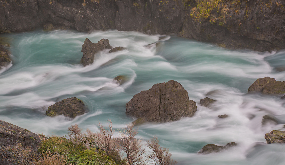 A pristine glacial river flows gracefully over boulders near Salto Grande, a waterfall in Torres del Paine National Park, Chile.