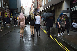 Portland Place, London, June 25th 2016. Thousands of LGBT people and their supporters gather for Pride in London, a colourful celebration of the hard-won rights of lesbian, gay, bisexual and transgender  people. PICTURED: Revellers make their way through the wet streets of Soho