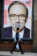 A man passes a poster signed by street artist Dr. D showing a portrait of News Corp head Rupert Murdoch in London. Britain's Culture Secretary Jeremy Hunt referred News Corporation's bid for BSkyB to the Competition Commission.