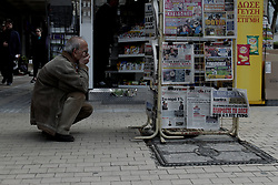 April 5, 2017 - Athens, Greece - A man kneels to read the newspapers at a kiosk, in central Athens on April 5, 2017  (Credit Image: © Panayotis Tzamaros/NurPhoto via ZUMA Press)