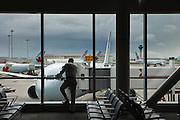 Man waiting at Toronto Airport,Canada, with Air Canada aircraft in background