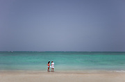 A mother and her daughter share a moment together on the clear blue ocean waters