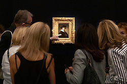 © Licensed to London News Pictures. 23/07/2020. London, UK. Visitors view a painting titled self portrait, wearing a ruff and black hat painting (1632) by artist Rembrandt Van Rijn with an estimate of £12-16 million. Works spanning over half a millennium of art history go on display at Sotheby's London ahead of a one-off auction on July 28. Titled 'Rembrandt to Richter', the sale will offer the very best from Old Masters, Impressionist & Modern Art, Modern & Post-War British Art and Contemporary Art – travelling from the Italian Renaissance through to Pop Art. Photo embargoed for usage until 24th July 2020 09:00. Photo credit: Ray Tang/LNP