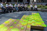 Office workers enjoy a lunchtime in Leadenhall in front of the artwork entitled Opening The Air by the artist Jyll Bradley, during the 2018 heatwave in the City of London, the capitals financial district, on 24th July 2018, in London, England. Opening the Air is a three-dimensional drawing made up of a geometric field of fluorescent Plexiglas discs or 'coins'. The coins bear intricate etchings derived from plans of early eighteenth-century glasshouse design and are planted on a low workaday wooden table.