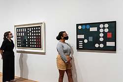 """© Licensed to London News Pictures. 13/07/2021. LONDON, UK. Staff members pose with  (L) """"Circle Picture"""", 1933, and """"Circle Picture"""", 1931. Preview of the first UK retrospective exhibition at Tate Modern of works by Sophie Taeuber-Arp (1889-1943), one of the foremost abstract artists and designers of the 1920s and 30s. Works from Taeuber-Arp's accomplished career as a painter, architect, teacher, writer, and designer of textiles, marionettes and interiors is on 15 July – 17 October 2021.  Photo credit: Stephen Chung/LNP"""