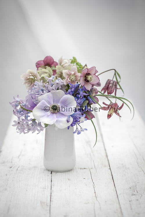 Spring flower arrangement with pale blue Anemone coronaria, hellebores, hyacinths and snake's head fritillarys