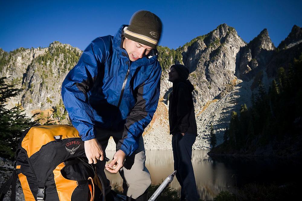 Brian Polagye packs his bag on the shore of Boulder Lake on an ascent of Hurricane Peak in Glacier Peak Wilderness, Washington.