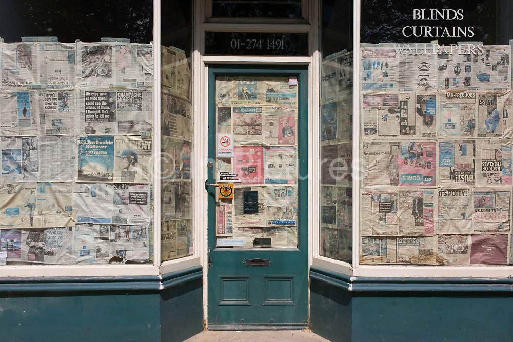 Newspaper obscures the windows and doorway of a closed shop business in south London. Faded headlines and news items on front and inside pages of local and national media now obscure the inside of this former home decor business in Herne Hill, SE24 in south London. The words Blinds, Curtains, Wallpapers with the old phone number have been stenciled on to the windows describing the life of these premises.