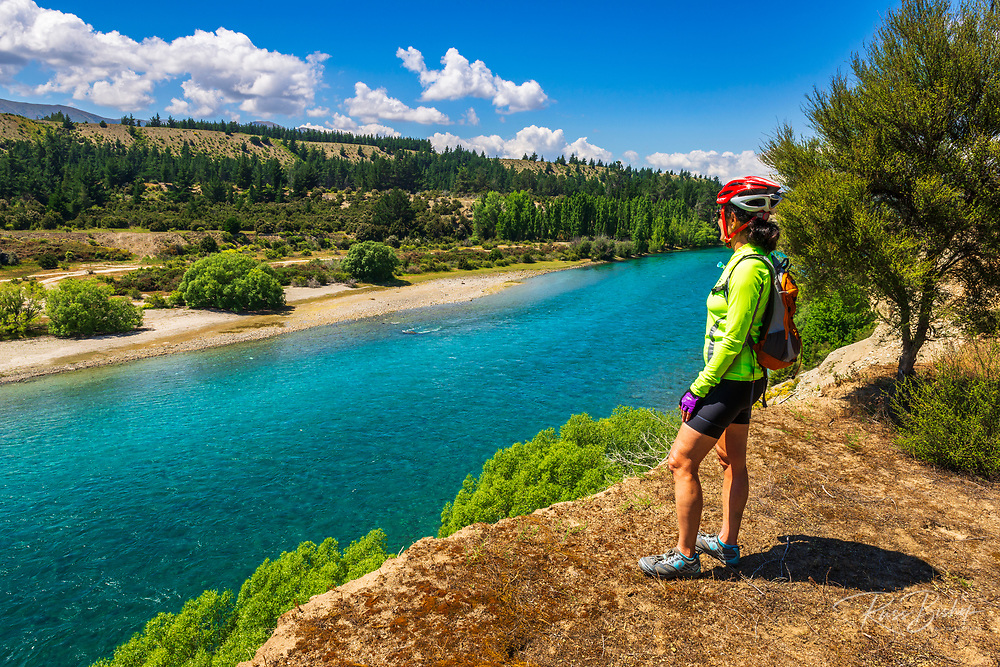 Cyclist enjoying the view from the Upper Clutha River Track, Central Otago, South Island, New Zealand