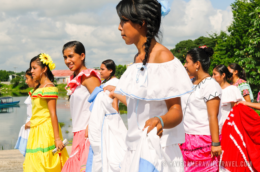 A group of young women dressed in traditional colonial dresses walk by as as part of the celebrations for Guatemalan Independence Day on 15 September 2011. Groups of school students parade in a procession through the streets of Flores, starting in the Parque Central, walking through the town, and crossing the causeway into Santa Elena.
